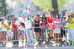 Onlookers at West Indian Day Parade. Patrons holding their flags and watching the West Indian Day Parade royalty free stock photography