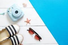 Onmiddellijke camera, gestreepte sandals, uitstekende glazen, zeeschelpen en zeester op witte houten achtergrond Toebehoren en kl stock fotografie