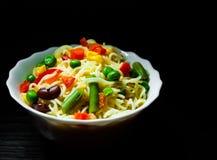 Onmiddellijke noedels met gemengde groenten in kom op donkere houten achtergrond met exemplaarruimte Stock Foto