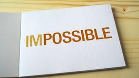 Onmogelijk wordt mogelijk door brieven langzaam te verdwijnen die op de notitieboekjepagina worden gedrukt stock video