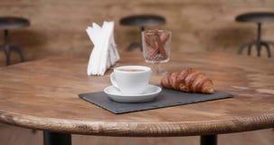 Ono ślizga się w minimalistycznym składzie kawa i croissant na ciemnej kamiennej tacy zdjęcie wideo