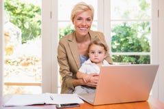 Ono uśmiecha się ładna blondynki kobieta z jego synem używa laptop Obraz Stock