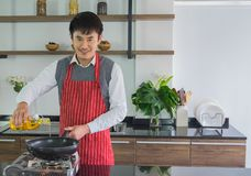 Ono uśmiecha się, Azjatycki młody człowiek Nalewa olej na niecce dla przygotowywać jedzenie w kuchni w domu zdjęcia royalty free