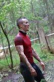 Ono uśmiecha się, mięśniowy mężczyzna w czerwonej koszula zakrywającej z błotem Obraz Stock
