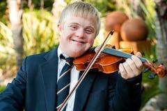 Ono uśmiecha się niepełnosprawna chłopiec bawić się jego skrzypce. Zdjęcia Royalty Free