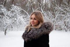 Ono uśmiecha się, radosna młoda kobieta w zimie w parku Blondynka w zima żakieta odprowadzeniu w parku Obrazy Royalty Free