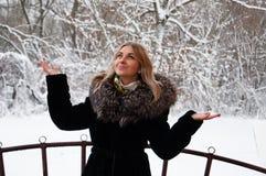 Ono uśmiecha się, radosna młoda kobieta w zimie w parku Blondynka w zima żakieta odprowadzeniu w parku Fotografia Stock