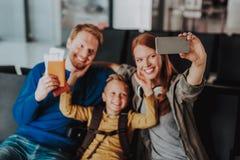 Ono uśmiecha się rodzice z chłopiec biorą selfie przy lotniskiem obraz royalty free