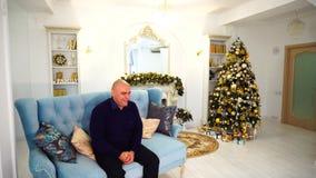 Ono uśmiecha się szeroko dorosły dostojny mężczyzna i ojciec siedzi na błękitnej kanapie w świątecznym dekorującym który pozuje i zbiory wideo