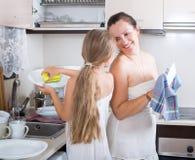 Ono uśmiecha się z córki cleaning crockery Zdjęcie Royalty Free