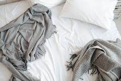 Onopgemaakt bed met hoofdkussen en grijze dekens hoogste mening stock afbeelding