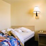 Onopgemaakt bed in motel. stock afbeelding