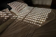 Onopgemaakt tweepersoonsbed met cirkelpatronen van het gesloten blind stock afbeelding