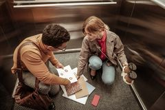 Onoplettende vrouw het dalen documenten op de vloer in lift royalty-vrije stock fotografie