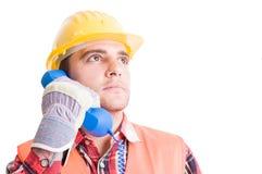 Onrealistische en zekere bouwer die telefoon met behulp van Stock Foto's