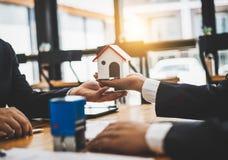 Onroerende goederen het huis verkoopt agent herziet de documenten die voor de lening van de huiskoper zijn goedgekeurd royalty-vrije stock fotografie