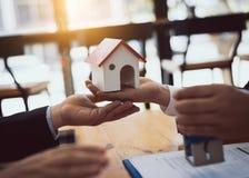 Onroerende goederen het huis verkoopt agent herziet de documenten die voor de lening van de huiskoper zijn goedgekeurd stock foto's