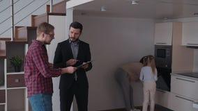 Onroerende goederen het spreken met vader van familie over nieuw huis voor Re stock video