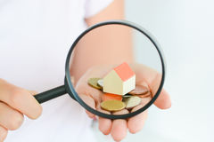 Onroerende goederenconcept - muntstukken en huis architecturaal model in vrouwenhand onder vergrootglas Stock Foto's