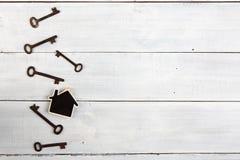 Onroerende goederenconcept - weinig huis en sleutels op wit houten bureau Stock Afbeeldingen