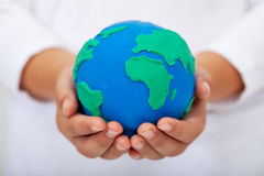 Ons huis - de aarde van de kindholding die van klei wordt gemaakt stock fotografie
