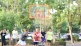 Onscherp beeld van bejaarden, tienerjaren en vrouwen die basketbal in de ochtend spelen bij BangYai-Park, Nonthaburi in Thailand stock footage