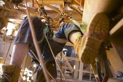 Onscherp beeld van de mijnwerker van de kabeltoegang het werken bij hoogte hangin bij twee kabel beginnen die stap voor stap gebr stock fotografie