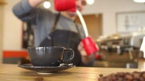 Onscherp beeld van een mens die een geurige latte in een koffiewinkel maakt, giet hij melk stock video