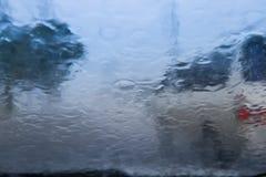 Onscherp die autosilhouet door waterdalingen wordt gezien op de auto windsh Royalty-vrije Stock Foto