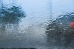 Onscherp die autosilhouet door waterdalingen wordt gezien op de auto windsh Royalty-vrije Stock Foto's