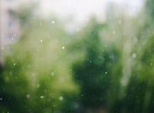 Onscherpe regendruppels op de abstracte achtergrond van het vensterglas stock foto's