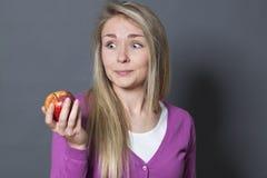 Onschuldige gefascineerd jaren '20meisje die smakelijke appel met afgunst houden stock foto