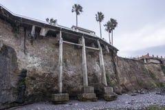 Onstabiele overzeese klip die onder huis eroderen Stock Afbeeldingen