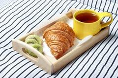Ontbijt in bed, Houten dienblad met thee, croissant en fruit royalty-vrije stock afbeeldingen