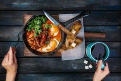 Ontbijt binnen op een hete pan met gebraden eieren, worsten, bonen, groen en toosts Vrouwen` s handen met koffie en Stock Afbeelding