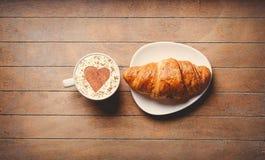 Ontbijt croissaint dichtbij kop van koffie op houten lijst Stock Foto's