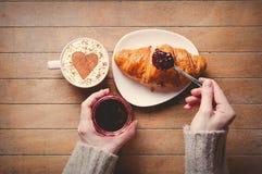 Ontbijt croissaint dichtbij kop van koffie op houten lijst Royalty-vrije Stock Afbeelding