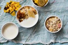 Ontbijt: eigengemaakte granola, banaan, verse bessen, yoghurt op lichte textielachtergrond Het high-carbon concept het gezonde et stock afbeelding