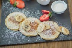 Ontbijt in het restaurant, pannekoeken met bessen met gepoederde suiker worden bestrooid die Royalty-vrije Stock Afbeeldingen