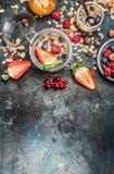 Ontbijt in kruiken Muesli met aardbeien en andere verse bessen, noten en zaden op rustieke achtergrond stock afbeelding