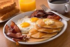 Ontbijt met bacon, eieren, pannekoeken, en toost