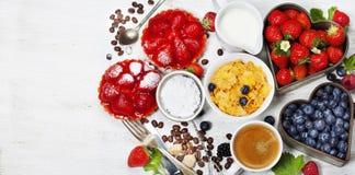 Ontbijt met koffie, cornflakes, melk, tartlets en bes stock afbeeldingen