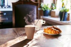 Ontbijt met kop hete koffie en verse croissants Stock Afbeeldingen