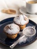 Ontbijt met muffins met gepoederde suiker op donkerblauwe plaat royalty-vrije stock fotografie