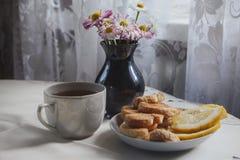 Ontbijt met thee, koekjes en citroen, op een wit tafelkleed, tegen een achtergrond van een vaas met madeliefjes Stock Foto's