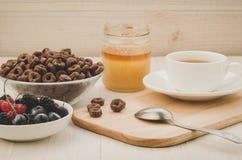 Ontbijt met verse bessen, vlokken, honing en een kop thee/ontbijt met verse bessen, vlokken, honing en een kop thee op a royalty-vrije stock fotografie