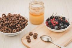ontbijt met vlokken, bessen, honing/ontbijt met vlokken, bessen, honing op een houten dienblad royalty-vrije stock foto