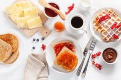 Ontbijt met wafel, uitgespreide toost, bes, jam, chocolade en c stock fotografie