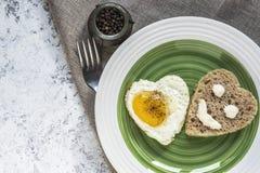 Ontbijt op de Dag van Valentine - gebraden eieren en brood in de vorm van een hart Smiley op een stuk van brood Hoogste mening royalty-vrije stock foto's