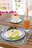 Ontbijt op de houten lijst: zonnige kant op eieren en roomchee Stock Foto's